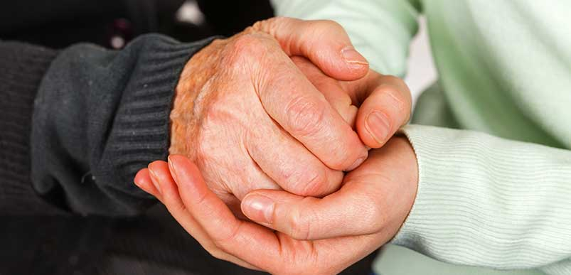 A closeup of an elderly person holding the hands of a younger person