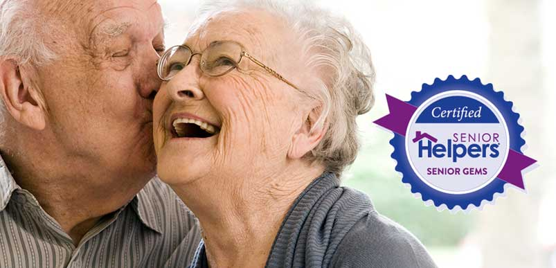 A senior woman smiling and getting kissed on the cheek by her husband