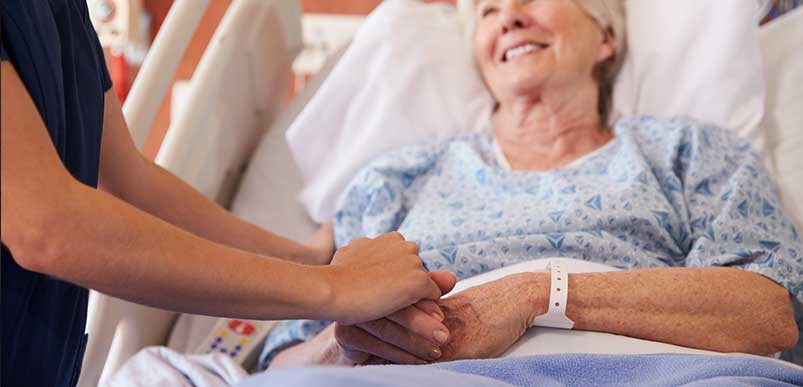 An elderly patient in a hospital bed smiling and looking at her nurse