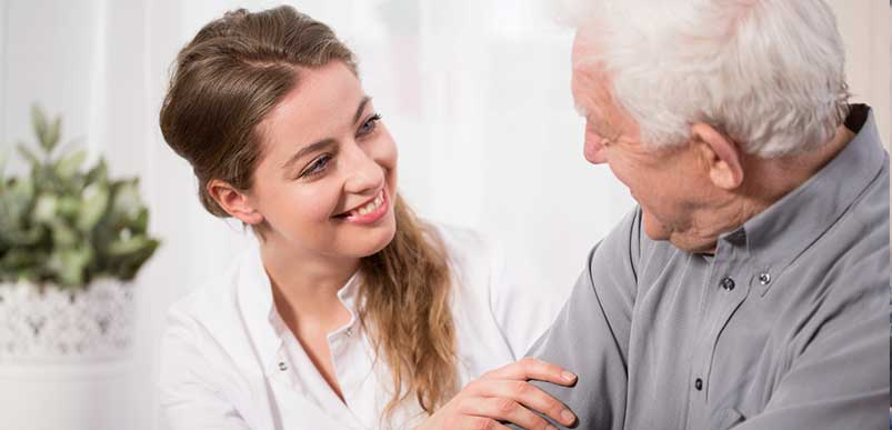 A caregiver and an elderly person smiling and looking at each other